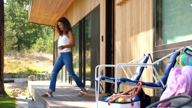 ms woman moving bags from front porch into vacation home - jeans stock videos & royalty-free footage