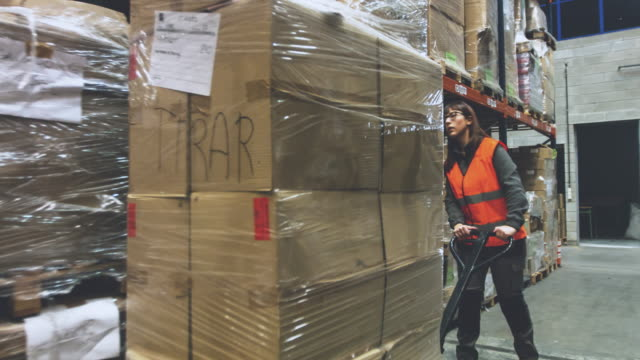 frau bewegen kartons im lager - hubwagen stock-videos und b-roll-filmmaterial