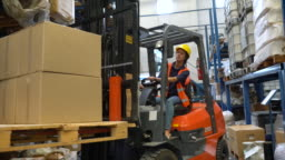 Woman moving cargo with forklift truck warehouse