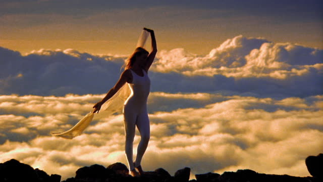 Woman moving gracefully holding sheet blowing in wind / sea of clouds below her in background / Hawaii