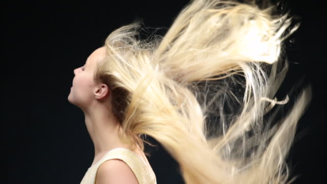 MS SLO MO Woman moving head with long blond hair moving in wind / London, Greater London, United Kingdom
