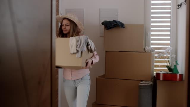 vídeos de stock, filmes e b-roll de mulher movendo-se em sua nova casa - embalagem cartonada