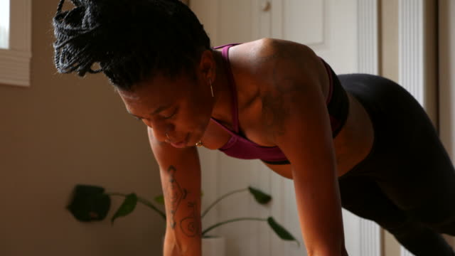 ts woman moving into downward facing dog pose while practicing yoga in home - athleticism stock videos & royalty-free footage