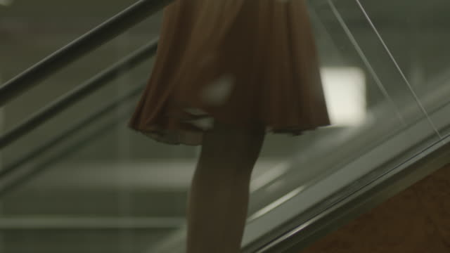 woman moving up an escalator. - escalator stock videos & royalty-free footage