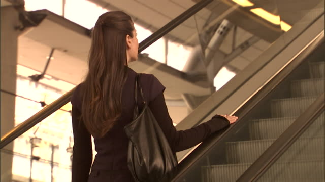 ms, la, woman moving up escalator, rear view, olympic park railway station, sydney, australia - escalator stock videos & royalty-free footage