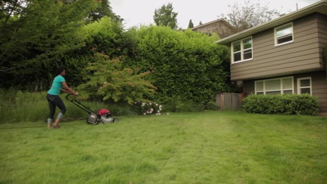 ms pan woman mowing backyard lawn / portland, oregon, united states - mowing stock videos & royalty-free footage