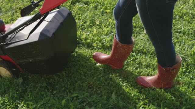 stockvideo's en b-roll-footage met slo mo vrouw maaien van het gazon - gras