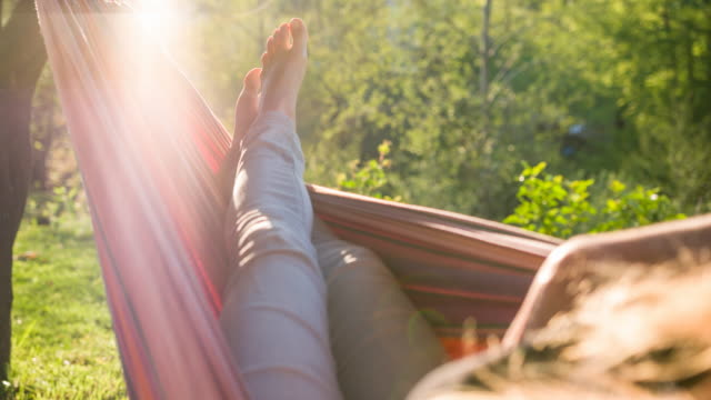 woman napping in a hammock, enjoying summer vacations - feet up stock videos & royalty-free footage