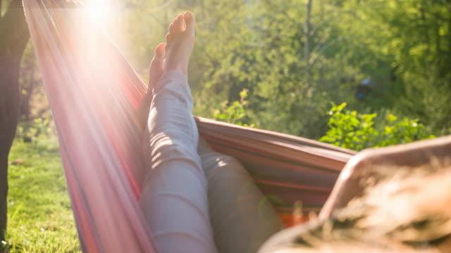 vídeos de stock, filmes e b-roll de mulher dormindo em uma cama de rede, aproveitando as férias de verão - de pé para cima