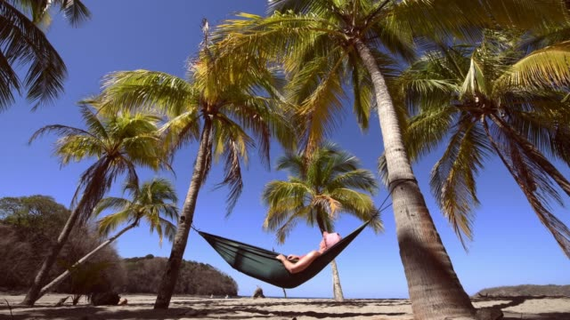 woman napping on hammock under palm trees in costa rica - costa rica video stock e b–roll
