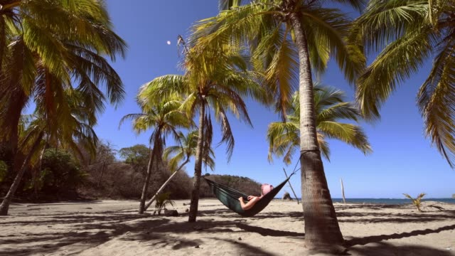 woman napping on hammock under palm trees in costa rica - costa rica stock videos and b-roll footage