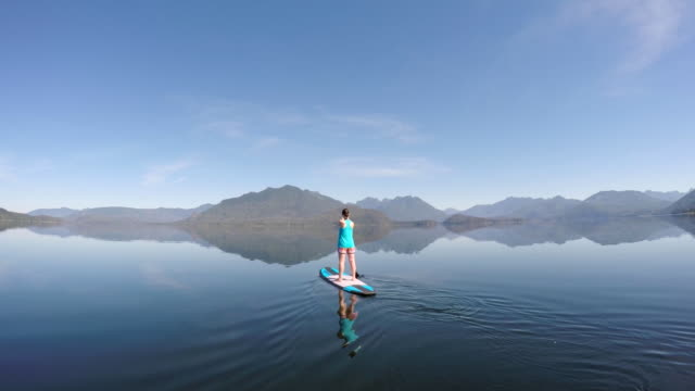 woman navigates stand up paddle board on ocean bay - using a paddle stock videos & royalty-free footage