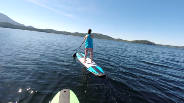 Woman navigates stand up paddle board on ocean bay