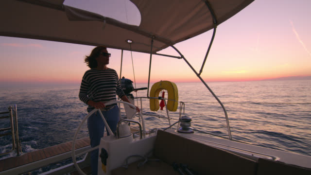 ws woman navigating a sailboat at dusk - sailing stock videos & royalty-free footage