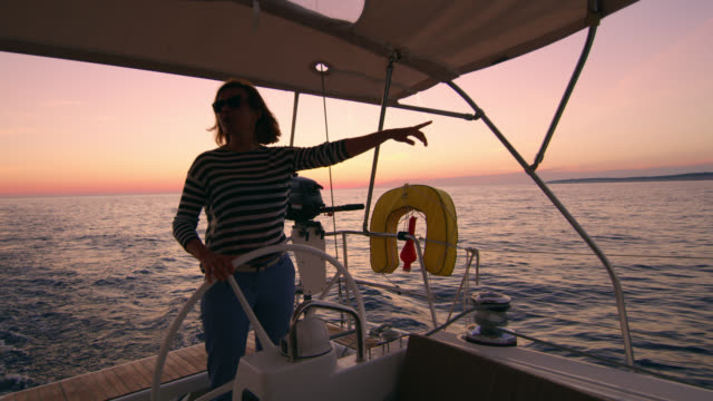 vidéos et rushes de femme de ws naviguer un voilier sur la mer au coucher du soleil - capitaine de bateau
