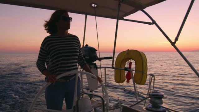 vidéos et rushes de woman ms naviguer un voilier - capitaine de bateau