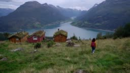 Woman near the huts in moss on the background of fjord