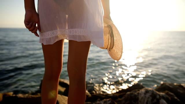 Femme près de l'océan. Coucher de soleil.