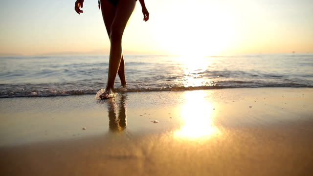 woman near the ocean.walking on the beach. footsteps in the sand - persona di sesso femminile video stock e b–roll