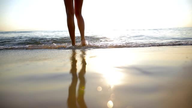 Femme près de l'océan. Marcher sur la plage. Traces dans le sable
