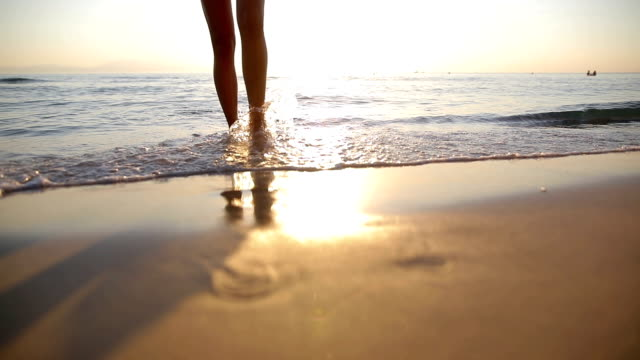 woman near the ocean.walking on the beach. footsteps in the sand - beach holiday stock videos & royalty-free footage