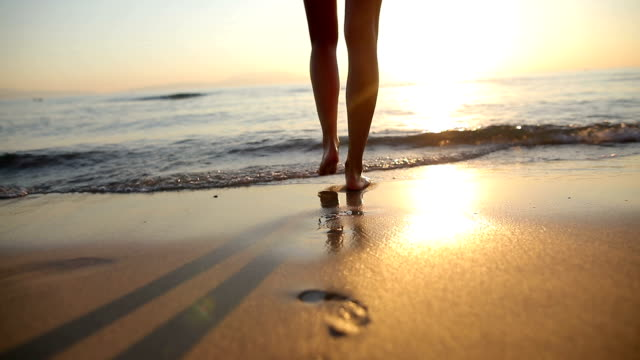 Woman near the ocean.Walking on the beach. Footsteps in the sand