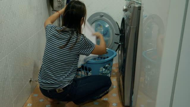 frau in der nähe von der waschmaschine reinigen - nur junge frauen stock-videos und b-roll-filmmaterial