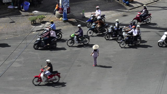 Woman negotiating a sea of mopeds during rush hour in central Saigon, Ho Chi Minh, Vietnam, Asia