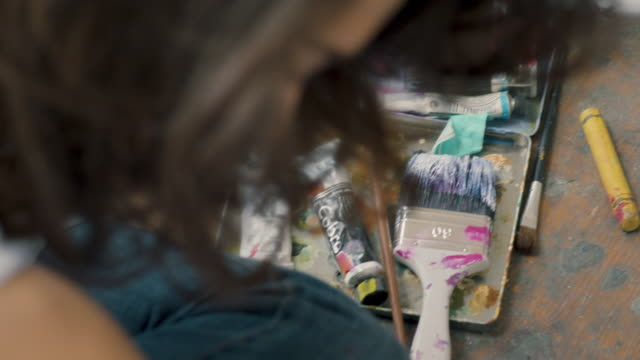 woman next to paintbrushes - 塗る点の映像素材/bロール