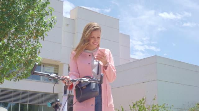 vídeos de stock, filmes e b-roll de a mulher observa seu telefone de pilha ao carreg uma bicicleta em sua mão - cultura jovem