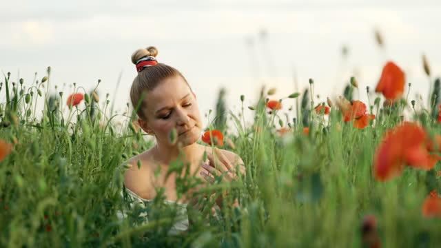 slow motion donna che osserva il fiore di papavero in mezzo al campo - vestito bianco video stock e b–roll