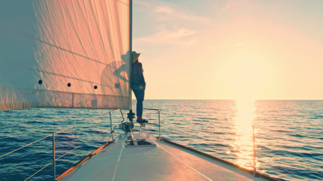 ws woman observing the sunset from a sailboat's bow - sailing boat stock videos and b-roll footage