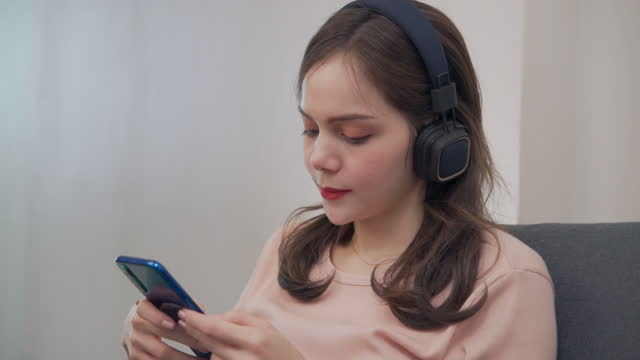 woman of asian descent, aged 20-30, chatting with a friend. via mobile phone or smartphone - tjänstekvinna bildbanksvideor och videomaterial från bakom kulisserna