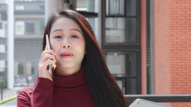 frau asiatischer abstammung, im alter von 20-30 jahren, mit handy oder smartphone - weibliche angestellte stock-videos und b-roll-filmmaterial