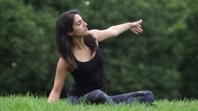 a woman of middle eastern descent practices yoga, alone in nature. - människoarm bildbanksvideor och videomaterial från bakom kulisserna