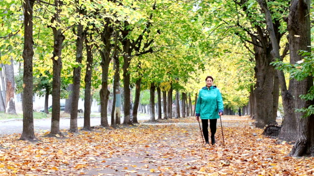 a woman of retirement age is practicing nordic walking. - ukrainian ethnicity stock videos and b-roll footage