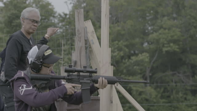 woman of unification church fires ar-15 at target range, slow motion medium shot - cult stock videos & royalty-free footage