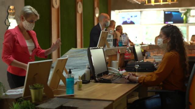 frauen-büro-empfangsmitarbeiterin im gespräch mit einer kollegin - sekretärberuf stock-videos und b-roll-filmmaterial