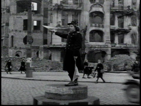 woman officer directing traffic in east berlin, the destroyed reichstag in the background / germany - 1948年点の映像素材/bロール