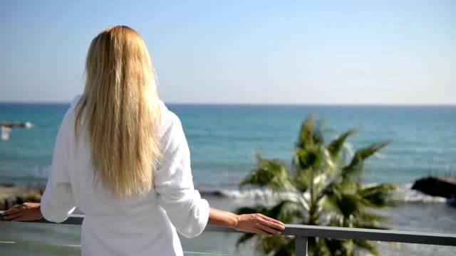 Woman on a balcony in bathrobe with sea view