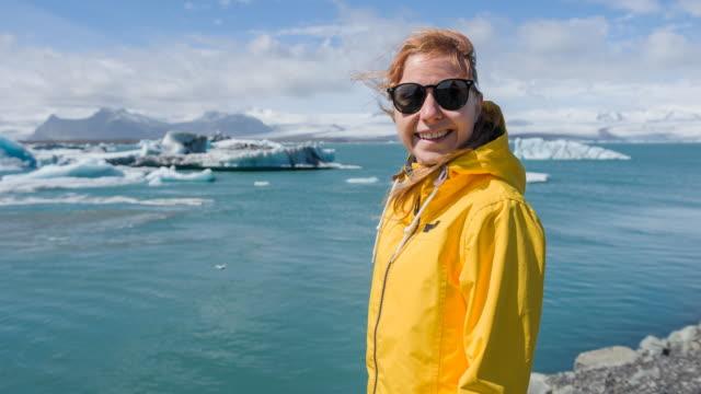 Woman on a beach admiring icebergs in water