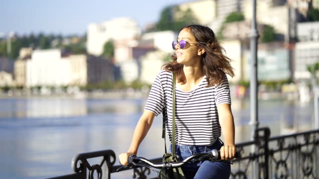 woman on a bicycle near a lake on a sunny day - top garment stock videos & royalty-free footage