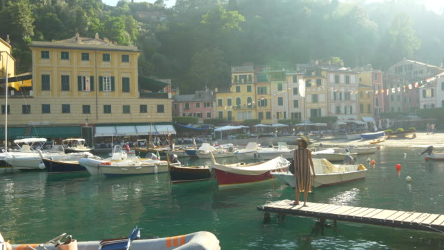 A woman on a boat dock in Portofino, Italy, a luxury resort town in Europe. - Slow Motion