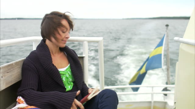 A woman on a boat reading a book Stockholm archipelago Sweden.