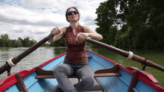 vídeos de stock, filmes e b-roll de woman on a boat rowing - sem manga