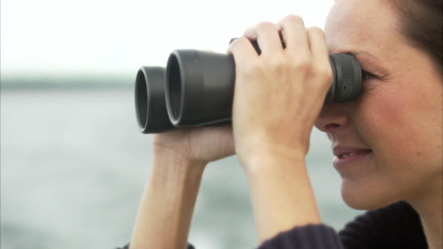 a woman on a boat using a pair of binoculars stockholm archipelago sweden. - canocchiale video stock e b–roll