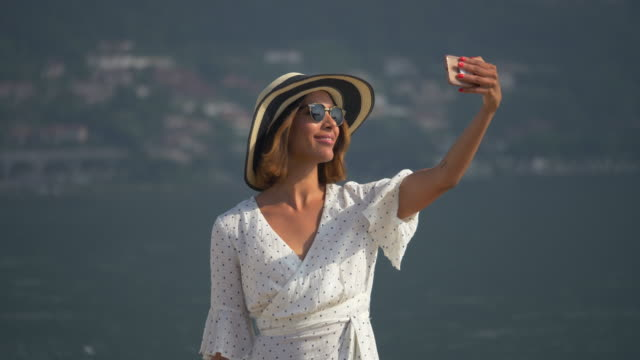 A woman on a classic luxury wooden boat taking selfie photographs. - Slow Motion