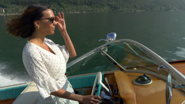 A woman on a classic luxury wooden runabout boat on an Italian lake.