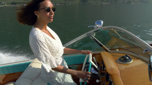 vídeos y material grabado en eventos de stock de a woman on a classic luxury wooden runabout boat on an italian lake. - slow motion - embarcación de recreo
