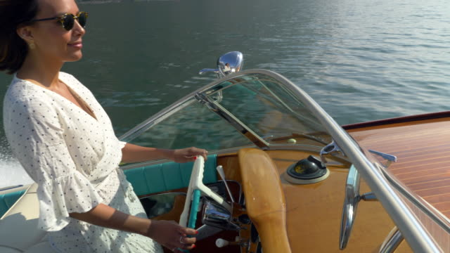 vídeos de stock e filmes b-roll de a woman on a classic luxury wooden runabout boat on an italian lake. - slow motion - riqueza